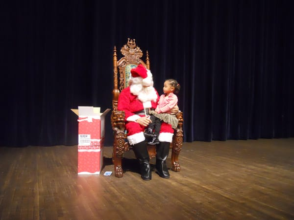 Santa listens while little Tyra Williams explains what she wants for Christmas.