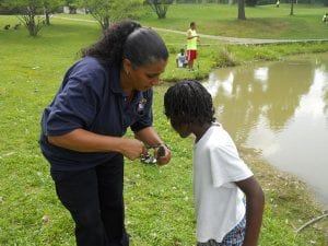 Officer Anna Mercada removes the hook from a fish caught that will be returned to the water.