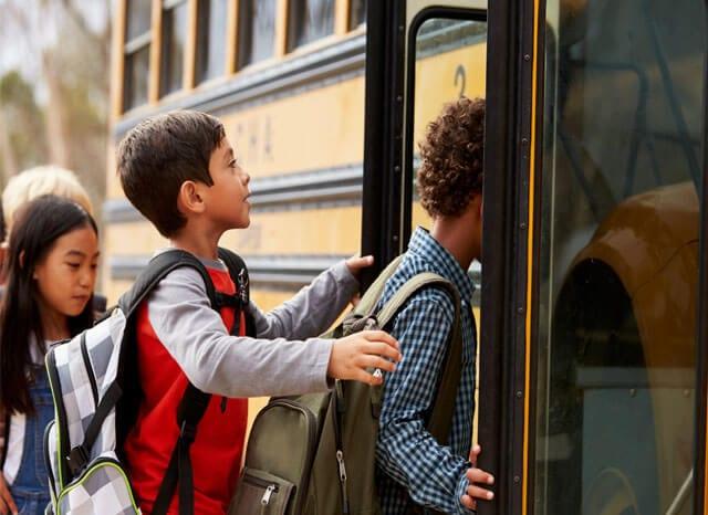children getting on bus