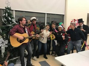 Officers in festive holiday gear join a guitarist and sing next to a Christmas tree in a community center space.