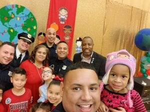 Officers pose with children in a school setting.