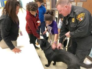 A child pets a police dog at a school.