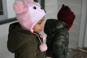 A child wearing a hat gazes in wonder at her new living space.