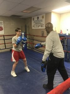 A young woman spars with an adult in a boxing ring.